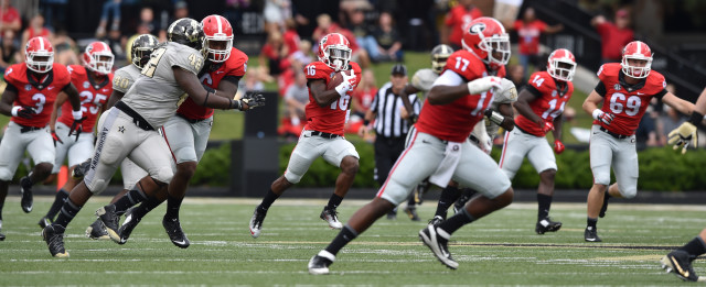 UGA wide receiver Isaiah McKenzie follows the lead of his blockers on the way to a 77-yard touchdown return on a punt in the first quarter. (Brant Sanderlin/ AJC)