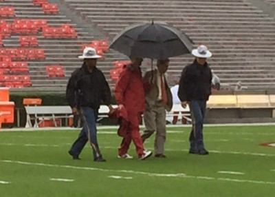 Alabama coach Nick Saban, his police escorts and umbrella holder check out the field conditions at Sanford Stadium. SPECIAL / BRITT THOMS