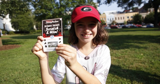Amanda Buckley poses with her $150 winning ticket. What a day this is turning out to be for such a young UGA fan. (Joshua L. Jones/ Special)