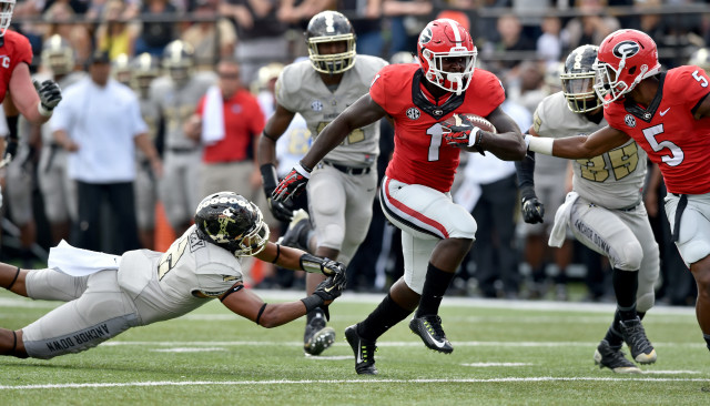 UGA running back Sony Michel eludes the tackle of Vanderbilt  safety Arnold Tarpley en route to a first half touchdown. (Brant Sanderlin/ AJC)