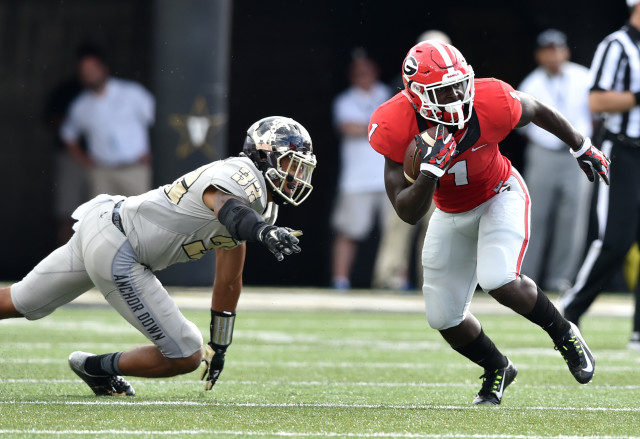 UGA running back Sony Michel eludes the tackle of Vanderbilt safety Andrew Williamson during the first half. Michel had a 31-yard touchdown run for Georgia in the second quarter. (Brant Sanderlin/ AJC)