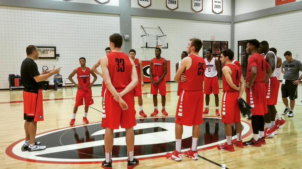 The Bulldogs huddle up around coach Mark Fox as they get set to begin their first practice of the 2015-16 season on Monday. UGA PHOTO