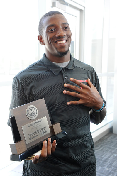 Mitchell shows off the Allstate AFCA Good Works trophy he unexpectedly received on Tuesday. UGA / JOHN KELLEY
